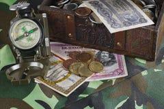 Een kist, een borst van muntstukken, oude bankbiljetten en een kompas op camouflagedoek, een onderzoek naar zeldzame vondsten Het royalty-vrije stock fotografie