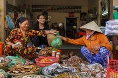 Een klant koopt vlees van een verkoper van de straatmarkt bij Nga-Baai, wedijvert Stock Afbeeldingen