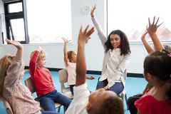 Een klasse die van de kinderen die van de zuigelingsschool op stoelen in een cirkel in het klaslokaal zitten, handen met hun vrou stock afbeeldingen