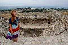 Een klassiek antiek Grieks theater in Pamukkale, Denizli, Turkije en een witte jonge vrouw in een hippie kleden zich stock foto