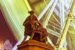 Een klassiek monument van een Griekse godinzitting voor ferris rijdt zich het bewegen met een motieonduidelijk beeld Royalty-vrije Stock Afbeelding