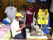 Een kleermaker werkt aan Jersey van een sport met zijn naaimachine Stock Foto