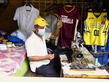 Een kleermaker werkt aan Jersey van een sport met zijn naaimachine Royalty-vrije Stock Foto's
