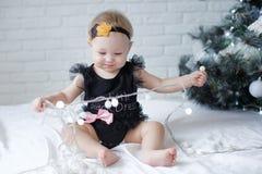 Een klein blauw-eyed meisje kruipt op een witte sluier tegen de achtergrond van een Kerstboom Stock Fotografie