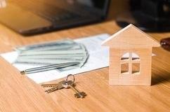 Een klein blokhuis bevindt zich op de lijst samen met een contract met een pen, gelddollars en flatsleutels stock afbeeldingen