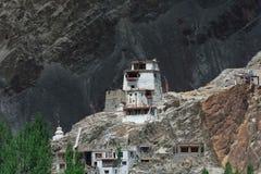 Een klein Boeddhistisch klooster bevindt zich op de rand van een klip tegen de achtergrond van een donkere bergmuur, Ladakh, Noor Royalty-vrije Stock Afbeelding