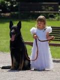 Een klein bruidsmeisje en haar hond. stock foto