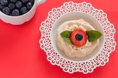 Een klein dessert van schuimgebakjepavlova met aardbei en munt hoogste mening stock foto's