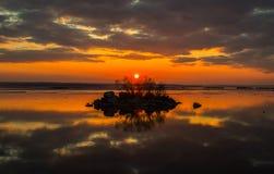 Een klein eiland op een achtergrond van zonsondergang Stock Afbeelding