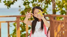 Een klein Filipijns schoolmeisje toont spinnende spinners Tropisch Landschap De zomer Kinderjaren stock afbeeldingen
