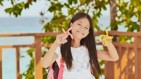 Een klein Filipijns schoolmeisje toont spinnende spinners Tropisch Landschap De zomer Kinderjaren royalty-vrije stock afbeelding