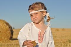Een klein gesierd meisje in slavic traditioneel chemise het eten van roggebrood in geoogst ingediend royalty-vrije stock afbeelding