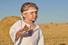 Een klein gesierd meisje in slavic traditioneel chemise het eten van roggebrood in geoogst ingediend stock afbeelding