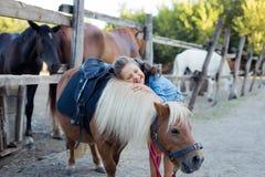 Een klein glimlachend meisje met krullend haar kleedde zich in jeans koesterend met een poney bij de stal royalty-vrije stock fotografie