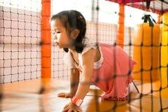Een klein glimlachmeisje kruipt bij speelplaats Stock Foto