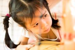 Een klein glimlachmeisje kruipt bij speelplaats Stock Foto's