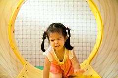Een klein glimlachmeisje kruipt uit gele tunnel bij playgrou Stock Afbeelding
