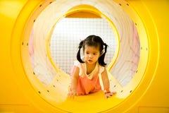 Een klein glimlachmeisje kruipt uit gele tunnel bij playgrou Stock Fotografie
