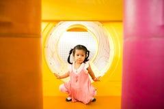 Een klein glimlachmeisje kruipt uit gele tunnel bij playgrou Stock Afbeeldingen