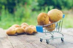 Een klein het winkelen karretje met aardappels op een oude houten lijst stock foto's