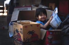 Een klein Indonesisch meisje die in een doos spelen Royalty-vrije Stock Fotografie