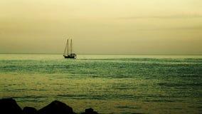 Een klein jacht op zee bij zonsondergang algemeen plan stock videobeelden