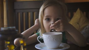 Een klein jong geitje die ontbijt hebben bij een comfortabele koffie Een aanbiddelijke meisje het drinken thee en het genieten va stock footage