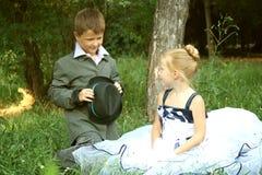 Een klein jongen en een meisje in een romantische scène Stock Foto's