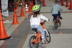 Een klein jongen en een meisje berijden fietsen op een speciale weg stock afbeeldingen