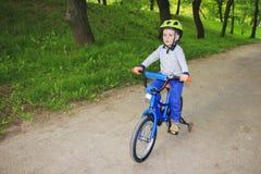 Een klein jongensjong geitje berijdt een kinderen` s fiets in een groen park in de zomer Stock Foto's