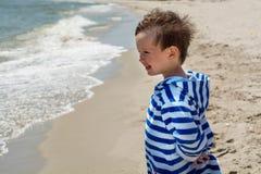 Een klein kind bevindt zich op de en kust die eruit zien glimlachen Stock Fotografie
