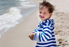 Een klein kind bevindt zich op de en kust die glimlachen eruit zien, Royalty-vrije Stock Fotografie