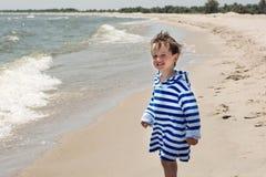 Een klein kind bevindt zich op de en kust die glimlachen eruit zien, Stock Fotografie