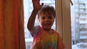 Een klein kind bij het venster glimlacht De close-up van het gezicht Zonlicht door het venster stock videobeelden