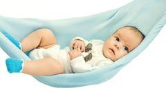 Een klein kind dat in een hangmat ligt Stock Afbeelding