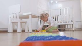 Een klein kind in de spelen van de de ruimtezitting van de kinderen met een multi-colored massagemat stock videobeelden