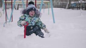 Een klein kind die met sneeuw in de winterpark spelen Kind die een schop, veel houden sneeuw in het Park Pret en spelen in stock videobeelden