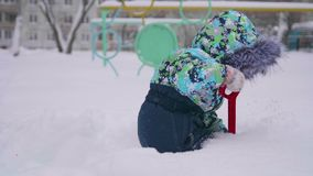 Een klein kind die met sneeuw in de winterpark spelen Kind die een schop, veel houden sneeuw in het Park Pret en spelen in stock footage