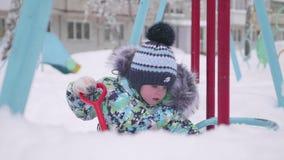 Een klein kind die met sneeuw in de winterpark spelen Kind die een schop, veel houden sneeuw in het Park Pret en spelen in stock video