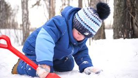 Een klein kind die met sneeuw in de winterpark spelen Zonnige de winter` s dag Pret en spelen in de verse lucht stock video