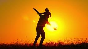 Een klein kind die op zijn vader` s schouders spinnen Het gelukkige familie spelen bij zonsondergang Silhouet stock footage