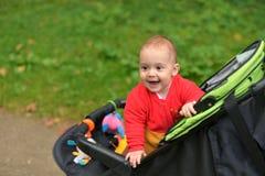Een klein kind die in overall in rolstoel en het glimlachen zitten stock afbeelding