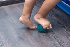 Een klein kind die zijn voeten masseren terwijl status op de het masseren bal royalty-vrije stock afbeeldingen