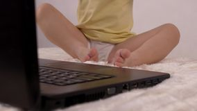 Een klein kind drukt een vinger op de knoop op het laptop toetsenbord, het close-up, de baby en de computer, ontspanning stock video