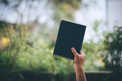Een klein kind drukte vreugde uit toen het ontvangen van een giftdoos Wanneer het houden van een notitieboekje en het steunen stock afbeelding