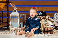 Een klein kind in een zitting van de denimkleding naast een bol stock afbeelding