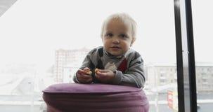 Een klein kind eet een kippenkarbonade op de achtergrond van een groot venster stock footage
