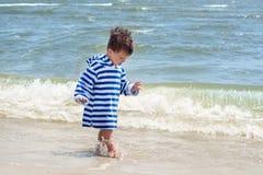 Een klein kind in een gestreepte robe bevindt zich op de kust in het water en bekijkt zijn natte benen om de wereld te kennen, Royalty-vrije Stock Afbeeldingen