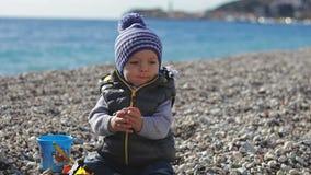 Een klein kind glimlacht in de camera en speelt op het strand met speelgoed stock video