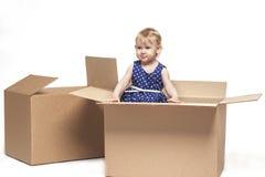 Een klein kind in kartondozen stock afbeeldingen